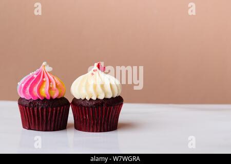 Süße Kuchen Dessert mit kleinen Herzen auf Weiß und Rainbow Creme auf rosa Hintergrund - Stockfoto