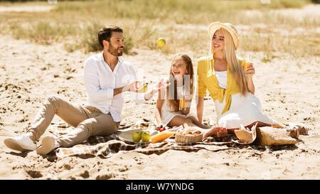 Eltern und kleine Mädchen mit Picknick in der Natur - Stockfoto