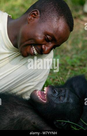 Tierarzt spielen mit ein waisenkind Bonobo (Pan paniscus) Lola Ya Bonobo Heiligtum, der Demokratischen Republik Kongo. - Stockfoto