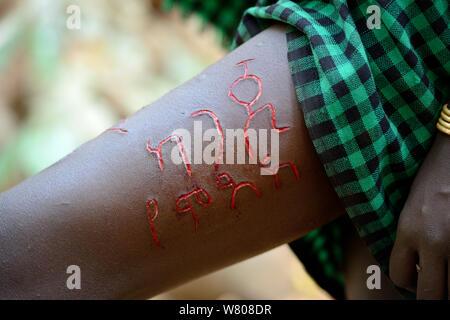Junge Frau aus der Bodi Stamm angezeigte aufwendige Haut scarifications auf ihr Bein, ihr Name im Amharischen Sprache, Omo Valley, Äthiopien, März 2015. - Stockfoto