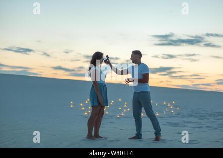 Der Kerl macht das Mädchen einen Heiratsantrag am Abend im Sand der Wüste. - Stockfoto