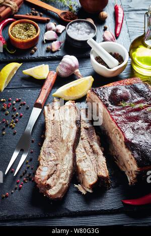 In der Nähe der Karibik geröstete Ruck Schweinebauch mit knusprige Haut auf schwarzem Schiefer Fach mit Zutaten im Hintergrund, vertikale Ansicht von oben - Stockfoto