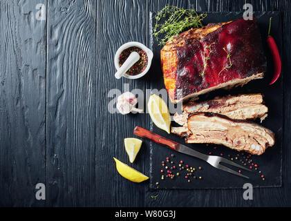 Karibik geröstete Ruck Schweinebauch mit knusprigen verkohlte Haut auf schwarzem Schiefer Fach, Ansicht von oben, flatlay, kopieren Raum - Stockfoto