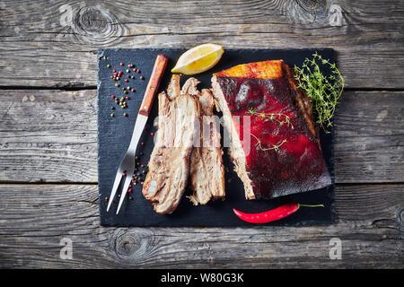 Karibik geröstete Ruck Schweinebauch mit knusprigen verkohlte Haut auf schwarzem Schiefer Fach auf einem alten Holz- rustikalen Tabelle, Ansicht von oben, flatlay, kopieren Raum - Stockfoto