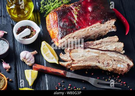Die jamaikanische geröstete Ruck Schweinebauch mit knusprige Haut auf schwarzem Schiefer Fach mit Zitrone, Gewürzen und frischem Thymian, horizontale Ansicht von oben - Stockfoto