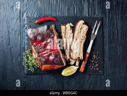 Karibik geröstete Ruck Schweinebauch mit knusprigen verkohlte Haut auf schwarzem Schiefer Fach, Ansicht von oben, flatlay, - Stockfoto