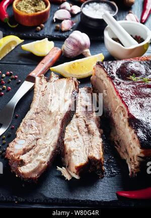 Nahaufnahme der Jamaikanischen geröstete Ruck Schweinebauch mit knusprigen verkohlte Haut auf schwarzem Schiefer Fach mit Zutaten im Hintergrund, vertikale Ansicht von Abo - Stockfoto