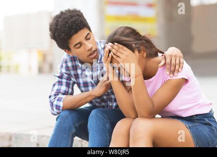 Junger Mann tröstet seine traurigen Freundin, dass Weinen auf öffentlichen - Stockfoto