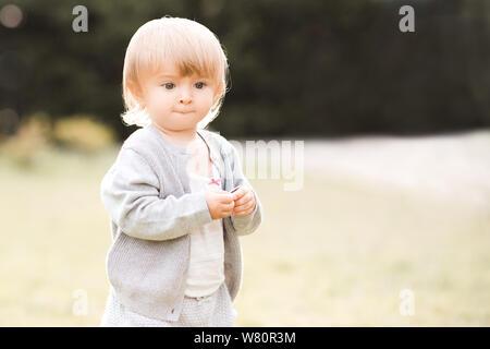Lustige Baby Mädchen 1-2 Jahre alten Walking im Park im Freien. Sommer Saison. Kindheit. - Stockfoto