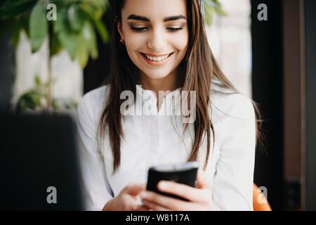 Schönen erwachsenen weiblichen Unternehmer mit einem Smartphone beim Sitzen in der Nähe von einem Fenster in Ihrem Büro. - Stockfoto