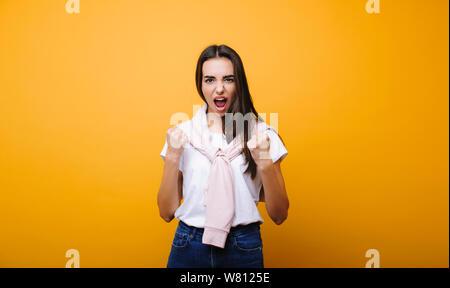 Attraktive erwachsene Frau schreien während den ersten Platz über Gelb Hintergrund isoliert zu gewinnen. Sieg Konzept! - Stockfoto