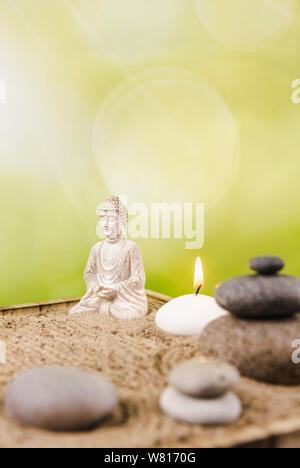Miniatur Schreibtisch zen Sandbox mit Buddha Figur sitzen im Lotussitz, gestapelte zen Meer Steine, Wellness Kerzen brennen gegen grüne Bokeh studio Hintergrund - Stockfoto