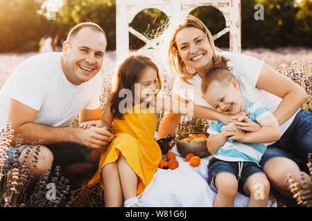 Porträt einer wunderschönen kaukasischen Familie sitzt in einem Lavendelfeld tun, ein Picknick mit Blick auf die Kamera umarmen und lachen und Spaß haben gegen Su - Stockfoto