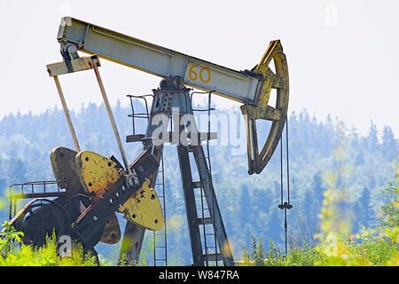 Öl- und Gas-Industrie. Arbeit von Öl Pumpe Jack auf einem Ölfeld. Weiße Wolken und blauer Himmel - Stockfoto