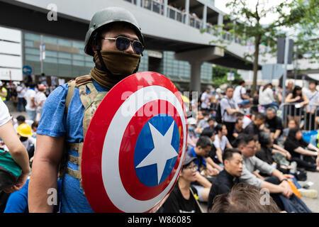 12. Juni 2019 während eines Anti Auslieferung Wechselprotest außerhalb der Regierung Büros in der Admiralität. Eine Demonstrantin in einem Captain America style Kostüm gekleidet, hält ein Schild. - Stockfoto