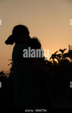 Die Silhouette eines Glückliche junge Mädchen die Arme seiner liebenden Mutter für eine Umarmung, vor dem Sonnenuntergang in den Himmel an einem Sommertag. - Stockfoto