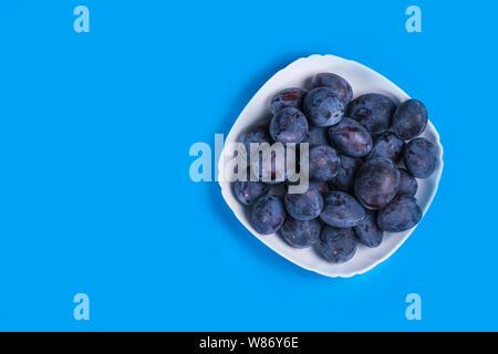 Frische Pflaumen auf einem weißen Teller auf einem blauen Hintergrund - Stockfoto