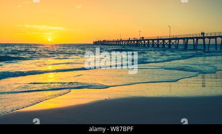 Port Noarlunga Bootsanleger mit Fischer bei Sonnenuntergang viwed von Strand, South Australia - Stockfoto