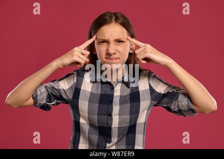 Schöne Mädchen im Teenageralter in einem zwanglosen kariertem Hemd posiert vor einem Pink Studio Hintergrund. - Stockfoto