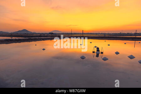 Frau Arbeiter sammeln frisch geerntete Salz in Körbe bei Sonnenaufgang in Hon Khoi Salz Feld, Nha Trang Provinz, Vietnam - Stockfoto