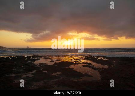 Lebendige, goldenen Sonnenaufgang über dem Kalkstein Küsten von El Medano, Teneriffa, Kanarische Inseln, Spanien. Mellow licht Sonnenaufgang über dem Atlantik. - Stockfoto