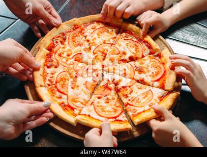 Hände, die pizza Scheiben aus Holz- Tabelle, Ansicht schließen. - Stockfoto
