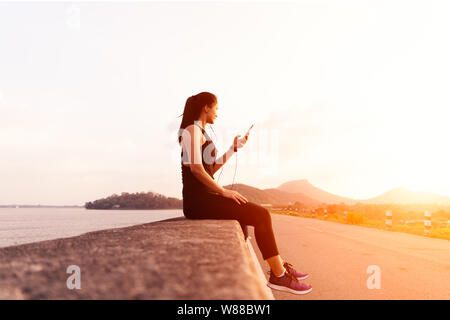 Seitenansicht des Sport Frau mit Kopfhörer sitzen auf der Wand nach einem Nachmittag laufen. Eine Athletin eine Pause nach einem Outdoor Training Stockfoto
