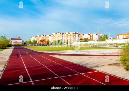 Dunkelrot links Laufbahn im Stadion gegen den blauen Himmel. - Stockfoto