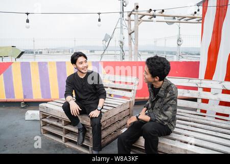 Zwei junge Mann sitzt auf dem Holzbrett - Stockfoto