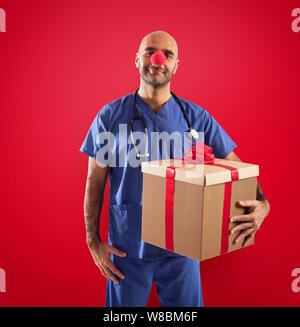 Krankenschwester mit clown Nase und Geschenk auf rotem Hintergrund - Stockfoto