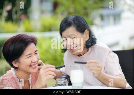 Tochter Altenpflege asiatische Frau, Kommissionierung ein chocolate cookie Mutter im Hinterhof. - Stockfoto