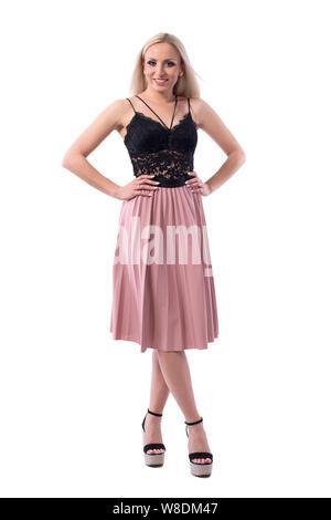 Süße hübsche blonde Frau in schwarzer Spitze oben und Lachs Farbe Rock mit Waffen auf den Hüften posieren. Voller Körper auf weißem Hintergrund. - Stockfoto