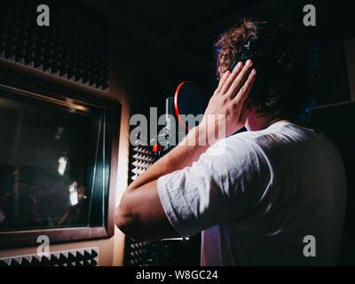 Vocal Artist mit lockigem Haar singen allein. Sänger Mann schreiben Song - Stockfoto