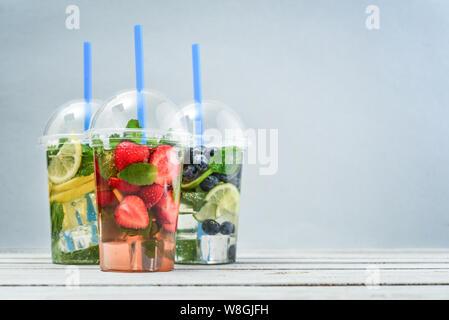 Verschiedene Limonade mit Früchten und Beeren in einen Plastikbecher mit Getränk Strohhalme auf blauem Hintergrund. Nehmen Getränke Konzept. - Stockfoto