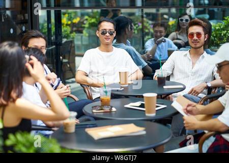 Jungen asiatischen nach Freunden entspannen im freien Kaffee shop - Stockfoto