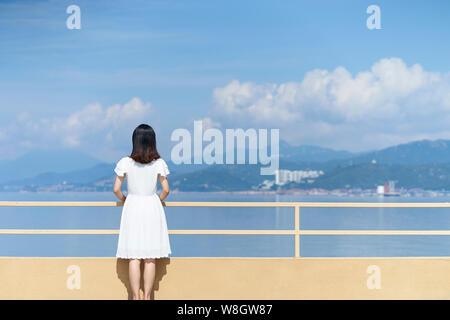 Rückansicht eines jungen asiatischen Frau im weißen Hemd am Meer - Stockfoto