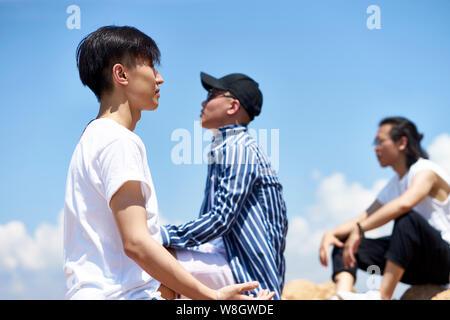 Gruppe von jungen asiatischen erwachsenen Männern saß oben auf der Felsen gegen den blauen Himmel Sonne und frische Luft genießen. - Stockfoto