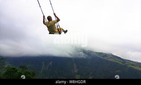 Junger Mann Spaß auf der Schaukel am Ende der Welt im Casa Del Arbol, Baumhaus in Banos, Ecuador - Stockfoto