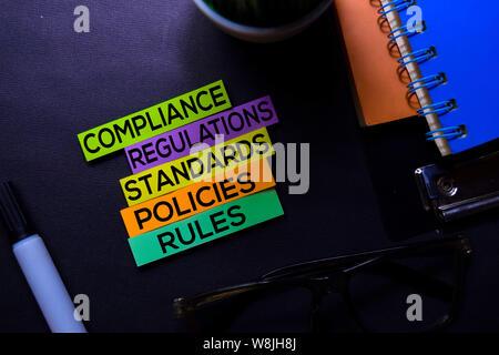 Einhaltung von Richtlinien, Verordnungen, Strandards, Richtlinien, Regeln text auf Haftnotizen auf Schwarzen Schreibtisch isoliert. Mechanismus Strategie Konzept