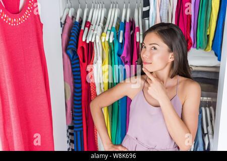 Home Schrank oder Store Kleidung rack Umkleideraum. Frau ihre Mode Outfit auswählen. Shopping Mädchen denken, was Vor vielen Entscheidungen der Kleider und Kleidung in organisierten sauber zu Fuß zu tragen. - Stockfoto