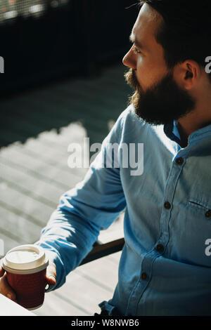 Ernte von bärtigen Mann im T-Shirt draussen sitzen mit geschlossenen Pappbecher mit Kaffee oder Tee und Wegsehen mit sonnendurchfluteten Plasterung auf unscharfen Ba - Stockfoto