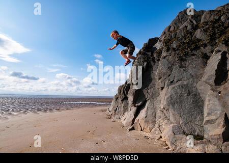 Ein Junge springt von einem hohen Felsen am Strand in der Nähe von Sandyhills, Dumfries und Galloway, der seine Fähigkeit in klettern und verwegen. - Stockfoto