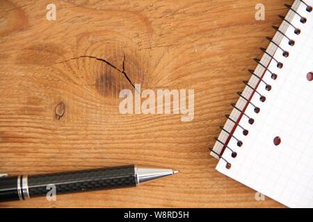 Leere Schreibblock mit Stift auf einem Holztisch - Stockfoto