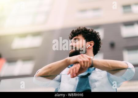 Erfolgreicher Mann in einem blauen Anzug steht in Anlehnung an das Geländer neben modernen Gebäuden, Ruhe im Freien. Weite Einstellung. Stockfoto