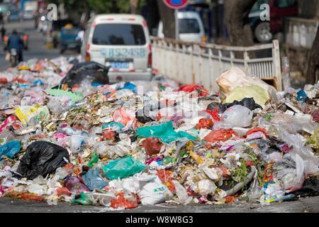 Ein minivan wird durch Berge von Müll auf der Straße in der bezirksfreien Stadt umgeben, Shenzhen, die südchinesische Provinz Guangdong, 20. November 2014. China - Stockfoto