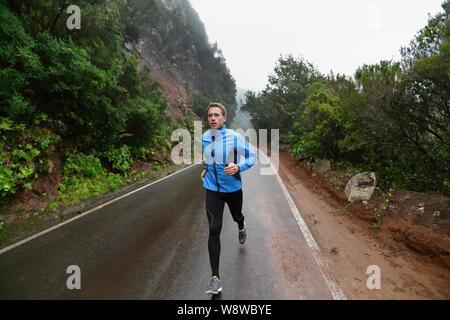 Männliche Läufer joggen und laufen auf der Straße im Regen in Jacke und lange Strumpfhosen. Fit fitness Modell Mann heraus arbeiten Leben gesunder Lebensstil Training für Marathon. Junge kaukasier Modell in seiner 20. - Stockfoto