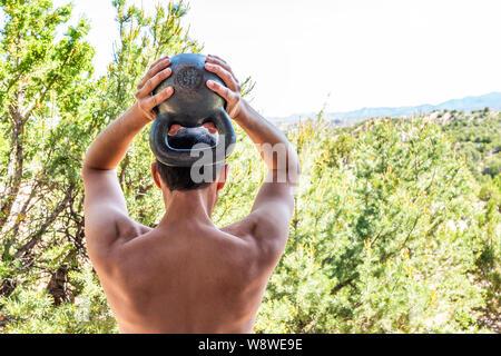 Zurück junger passen shirtless Mann mit schweren kettlebell tun Trizeps übung und Muskeln im Freien außerhalb Park holding Gewichtheben - Stockfoto