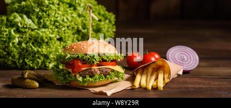 Leckeres vom Grill hausgemachte Burger mit Rindfleisch, Tomaten, Käse, Gurken und Kopfsalat. Köstliche gegrillte Burger. Handwerk Beef Burger und Pommes frites auf Holz - Stockfoto