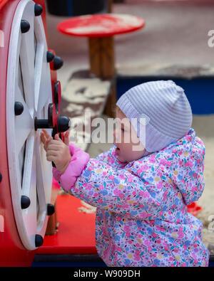 Kleines Mädchen auf dem Spielplatz. Ein Jahr alten Kind in einen Hut und Mantel spielt mit der Kinder Karussells und Sportgeräte. Ein Kind geht i - Stockfoto