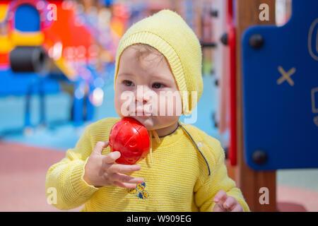 Ein Kind von einem kaukasischen Kaukasier spielt Sandformen in einer Sandbox. Kind Baby Mädchen Junge ein Jahr alten Spielen auf dem Spielplatz im Sandkasten. Portrait von - Stockfoto